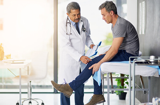 Doctor and patient reviewing symptoms of knee pain.